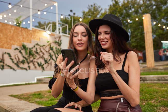 Amici in cappello nero divertendosi a guardare foto sul telefono cellulare seduto sul prato verde vicino al palco decorato nella giornata luminosa al festival — Foto stock