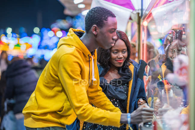 African American woman smiling and watching boyfriend catching toys in arcade game while spending evening on funfair together — Stock Photo