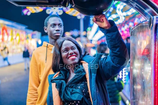 Afro americano pareja punching bola en funfair - foto de stock