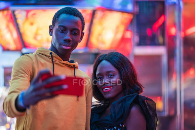 Black couple taking selfie on fairground — Stock Photo
