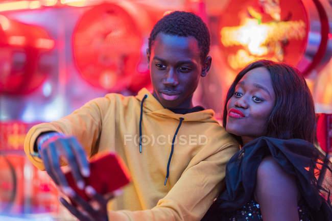 Black couple taking selfie on fairground — Stock Photo