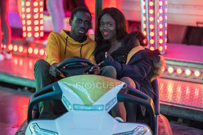 African American man and woman smiling and riding bumper car during date at night on fairground — Stock Photo