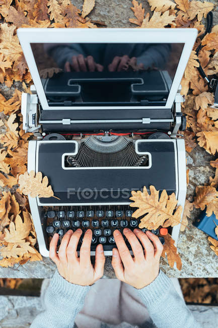 Hands of woman typing on vintage typewriter with tablet in autumn leaves on stone table in oak forest — Stock Photo