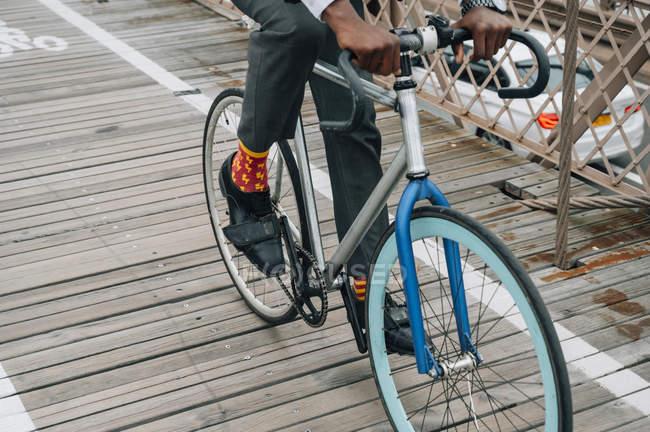 Imagen recortada de ciclista empresario bien vestido en bicicleta en camino de madera entre la estructura de metal rojo con en la ciudad de Nueva York - foto de stock