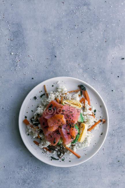 Da sopra gustoso salmone affettato appetitoso su riso bianco con verdure in piatto a tavola con spazio copia — Foto stock