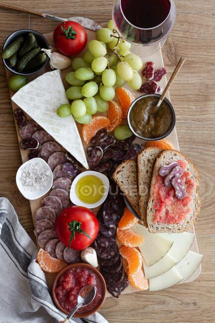 Vue du dessus de fruits frais colorés légumes de viande et sauces pour le vin à l'hôtel — Photo de stock
