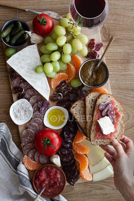 Von oben gesichtslose beschnittene Hände, die Snacks aus einem hölzernen Tablett mit Fleischstücken, Gemüsefrüchten und einem Glas Rotwein essen — Stockfoto