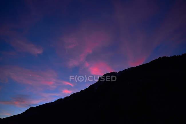 Розовые и фиолетовые облака перемещаются и бросают тень на горную цепь на закате в Испании — стоковое фото