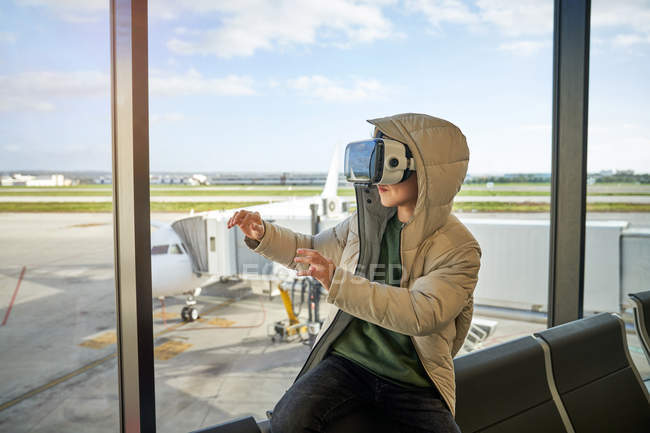 Preteen boy in hooded outwear and VR goggles gesturing and exploring virtual reality while sitting near window in modern airport — Stock Photo