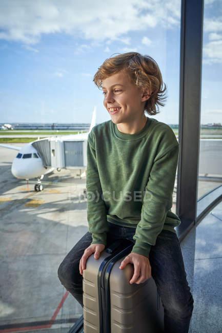 Menino pré-adolescente otimista em roupas casuais sorrindo e sentado na mala perto da janela no aeroporto contemporâneo olhando para longe — Fotografia de Stock