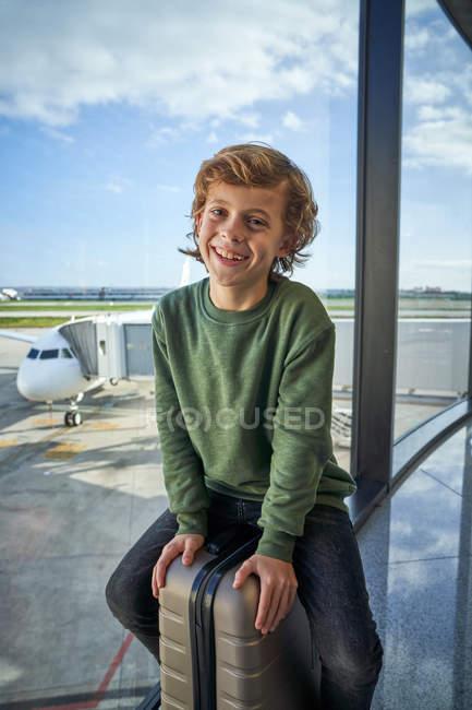 Préadolescent optimiste en vêtements décontractés souriant et assis sur la valise près de la fenêtre dans l'aéroport contemporain — Photo de stock