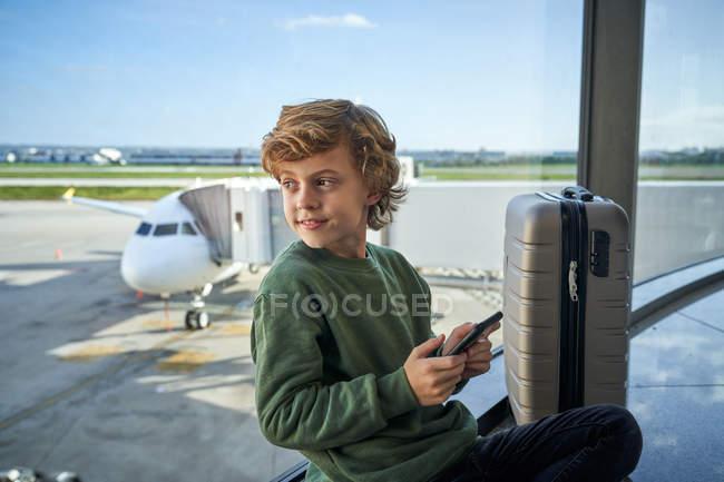 Enfant utilisant un smartphone assis sur le sol près de la fenêtre à l'aéroport — Photo de stock