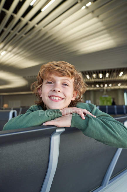 Boy relaxing on bench and looking at camera with dreamy glance while waiting for flight in modern airport — Stock Photo