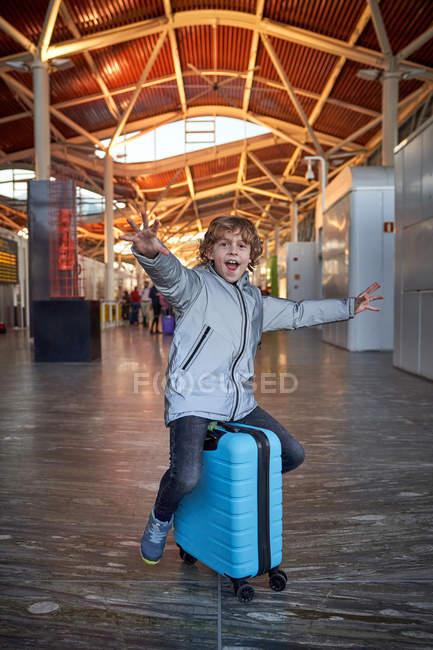 Allegro ragazzo preadolescente in abiti casual sorridente divertirsi con le braccia tese mentre seduto sulla valigia in aeroporto contemporaneo — Foto stock