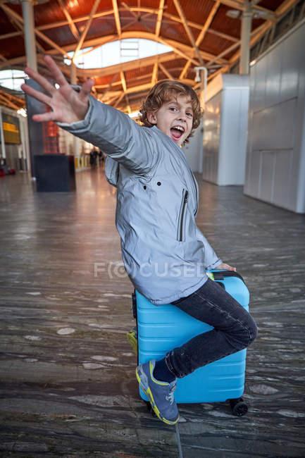 Веселый мальчик-подросток в повседневной одежде, улыбающийся, веселый с вытянутыми руками, сидя на чемодане в современном аэропорту — стоковое фото