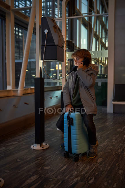 Preteen passenger sitting on luggage and speaking on telephone in evening in airport terminal looking away — Photo de stock