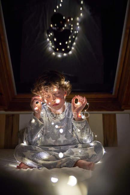 Маленький хлопчик у піжамі, закутаний у світлий гарбуз, вночі сидів на ліжку з закритими очима. — стокове фото
