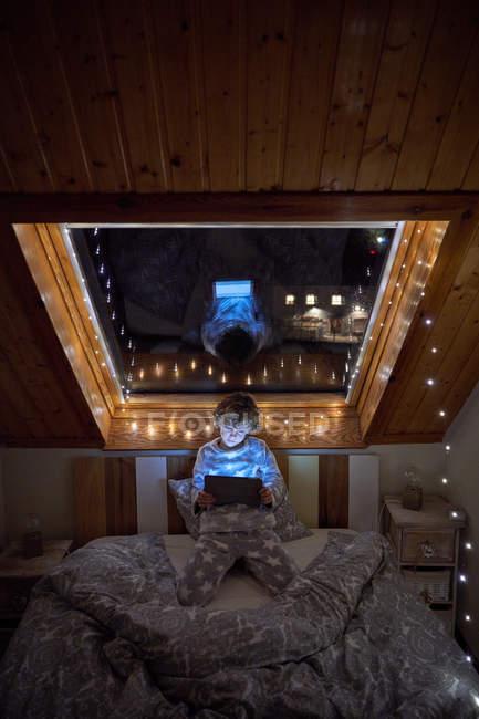 Petit garçon en pyjama naviguant tablette tout couché dans le lit près de la fenêtre du toit décoré avec des lumières de fées la nuit dans une chambre confortable — Photo de stock