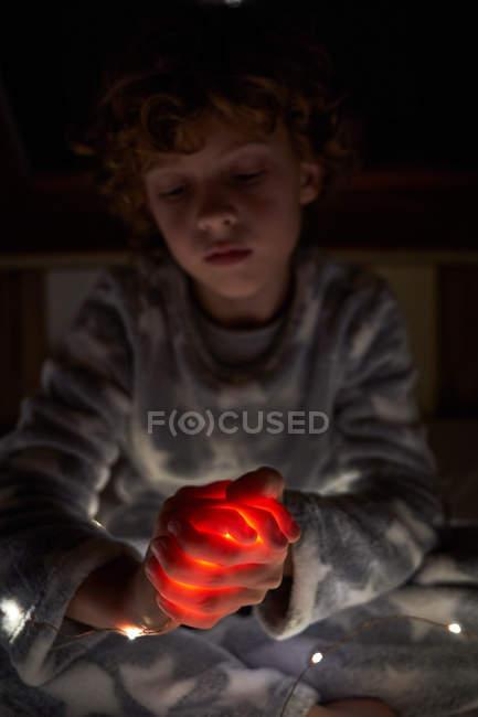 Nettes Kind mit geschlossenen Augen umklammert Hände mit hellem Licht und betet nachts mit — Stockfoto