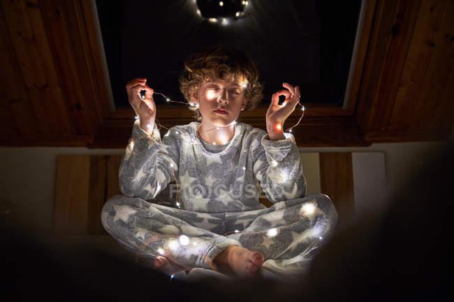 Niño en pijama envuelto en guirnalda ligera sentado con las piernas cruzadas en la cama por la noche en casa con los ojos cerrados - foto de stock