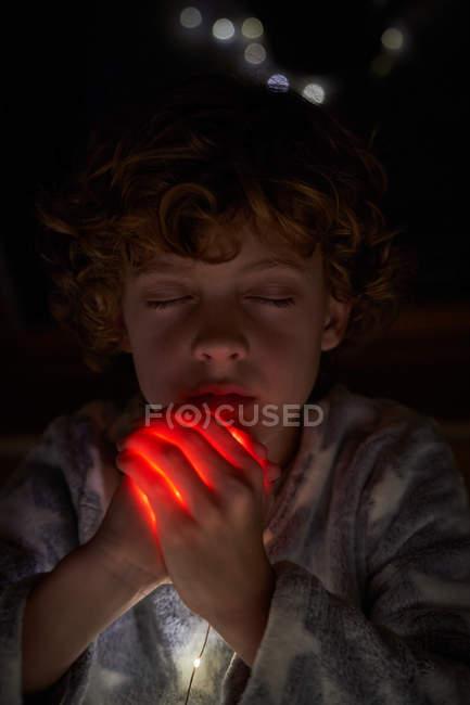 Мила дитина з заплющеними очима, що чіпляються за руки яскравим світлом і моляться вночі з — стокове фото