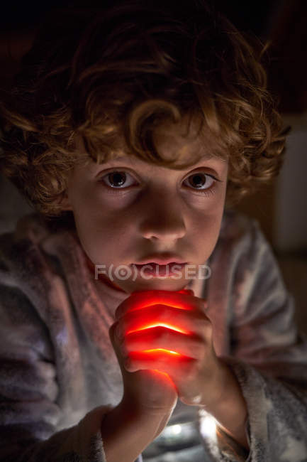 Cute child looking at camera clasping hands with bright light and praying at night with — Stock Photo