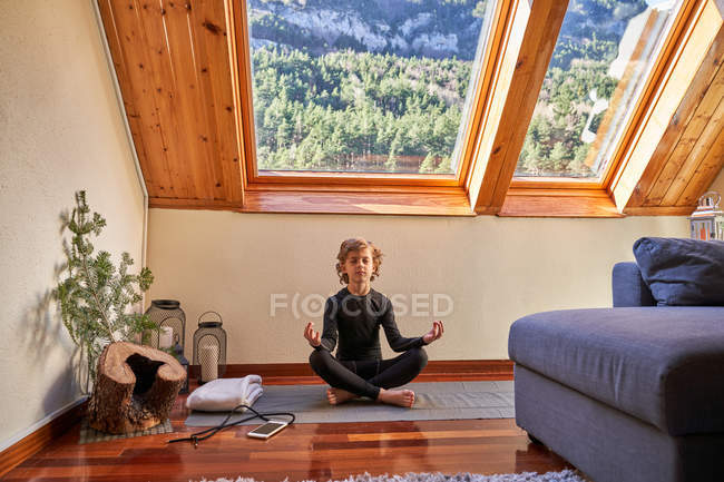 Little boy in black active wear sitting on mat in Lotus pose and meditating under window in cozy room at home — Stock Photo
