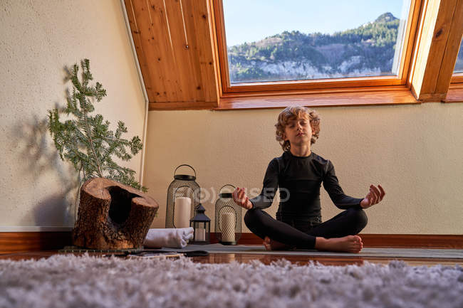 Little boy in black active wear sitting in lotus position doing yoga in the morning at home near big roof windows — Stock Photo