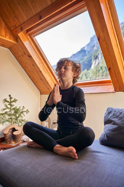 Хлопчик у чорному одязі сидить у позі лотоса і вранці робить йогу біля великих вікон даху. — стокове фото