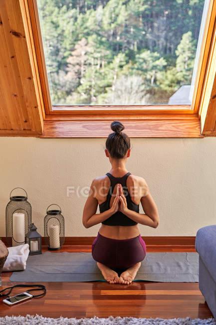 Вид сзади женщины в спортивной одежде, сжимающей руки за спиной, сидящей на коврике и занимающейся йогой под окном в уютной комнате — стоковое фото