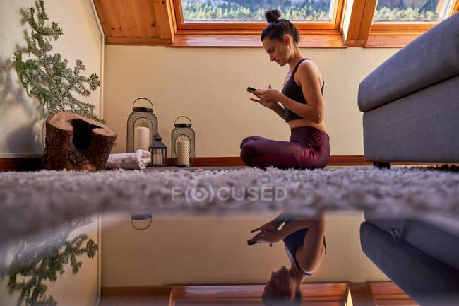 Vue latérale de la femme assise croisée pattes croisées sur le sol après avoir médité pendant l'entraînement de yoga à la maison en utilisant un téléphone mobile — Photo de stock