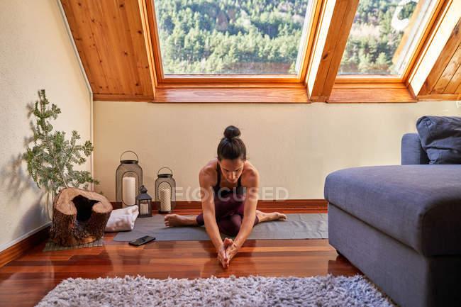 Стройная босиком женщина со скрещенными ногами наклоняется вперед, сидя на полу и занимаясь йогой утром дома — стоковое фото