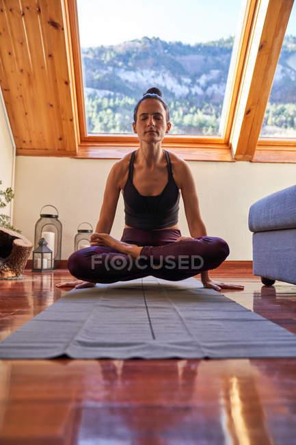 Стройная женщина с закрытыми глазами, поднимающая свое тело с пола, скрестив ноги во время медитации йоги тренировки дома — стоковое фото