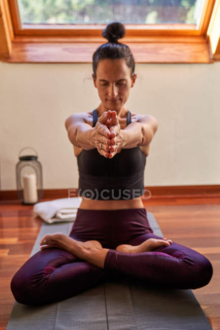 Slim woman with closed eyes and raised arm sitting crossed legged on floor and meditating during yoga workout at home — Stock Photo
