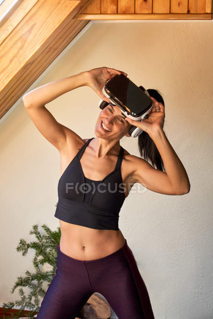 Cheerful fit woman in sportswear smiling looking away and taking off VR goggles during workout at home — Stock Photo
