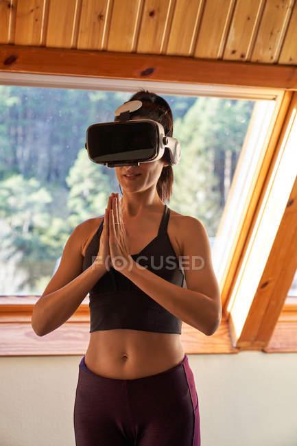 Frau mit Vr-Brille steht in Mountain-Pose mit gefalteten Händen, während sie morgens zu Hause Yoga macht — Stockfoto