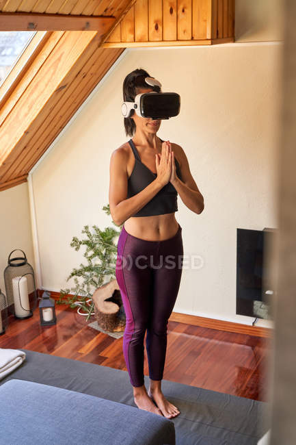 Woman in VR glasses standing in Mountain pose with clasped hands while doing yoga in morning at home — Stock Photo