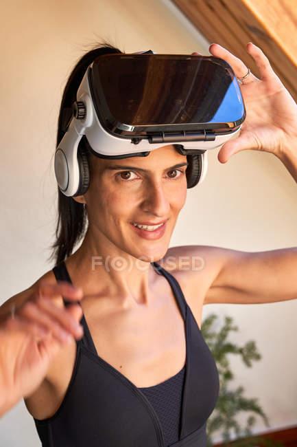 Веселая спортивная женщина в спортивной одежде улыбается перед камерой и снимает очки виртуальной реальности во время тренировки дома — стоковое фото