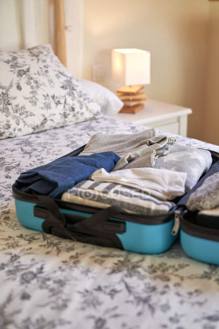 Packed suitcase on bed at home — Stock Photo