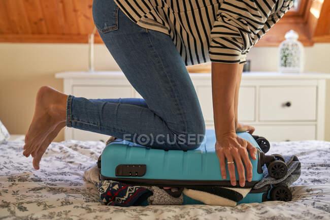 Crop femme fermeture des bagages dans la chambre — Photo de stock