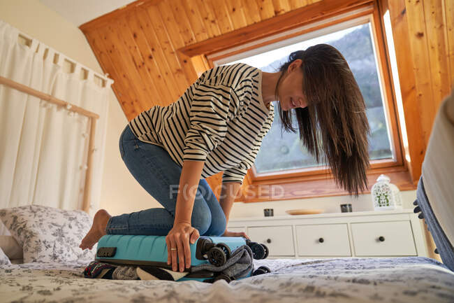 Woman closing luggage in bedroom — Stock Photo