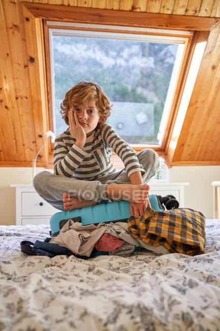 Niño aburrido sentado en el equipaje en la cama - foto de stock