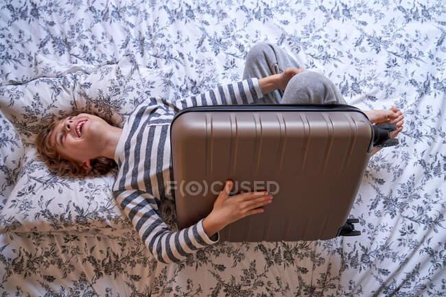 Chico alegre jugando con la maleta en la cama - foto de stock