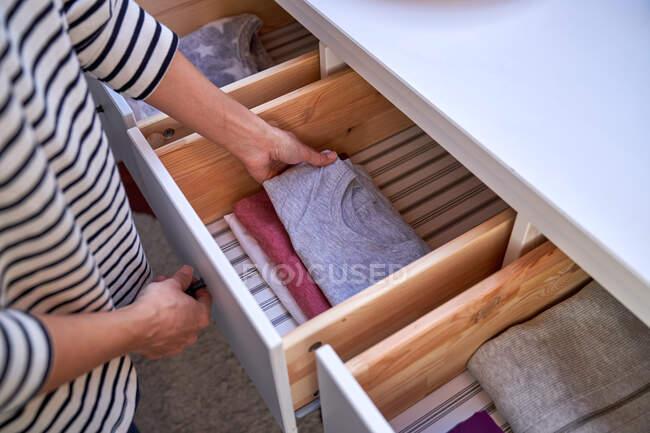 Mulher de colheita organizando roupas na gaveta — Fotografia de Stock