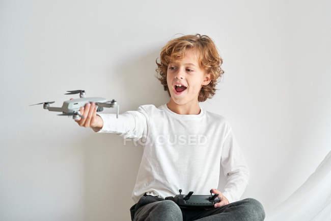 Niño manipulando un dron y el mando a distancia que le acaban de dar - foto de stock