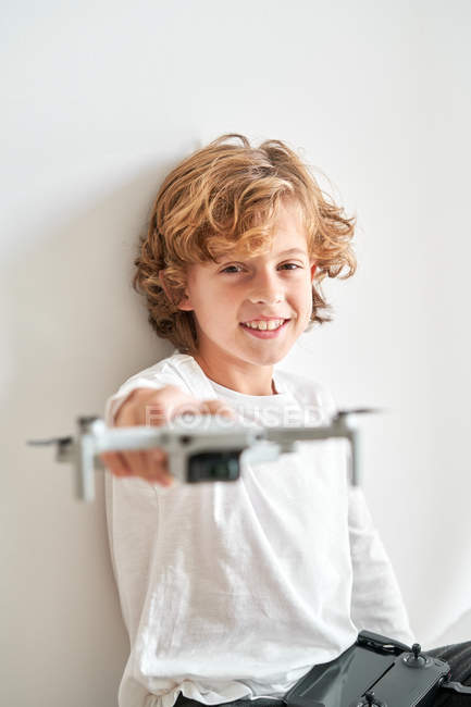 Child manipulating a drone and the remote control just given to him — Stock Photo