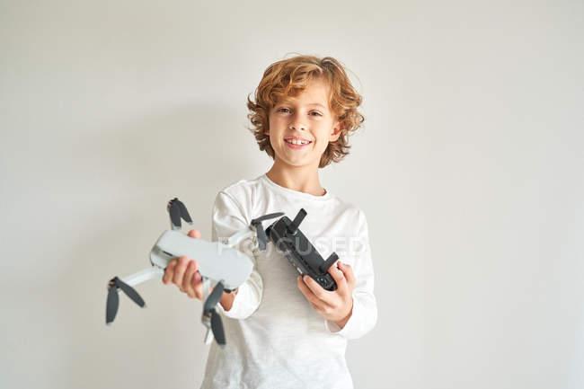 Kind manipuliert Drohne und die Fernbedienung, die ihm gerade gegeben wurde — Stockfoto