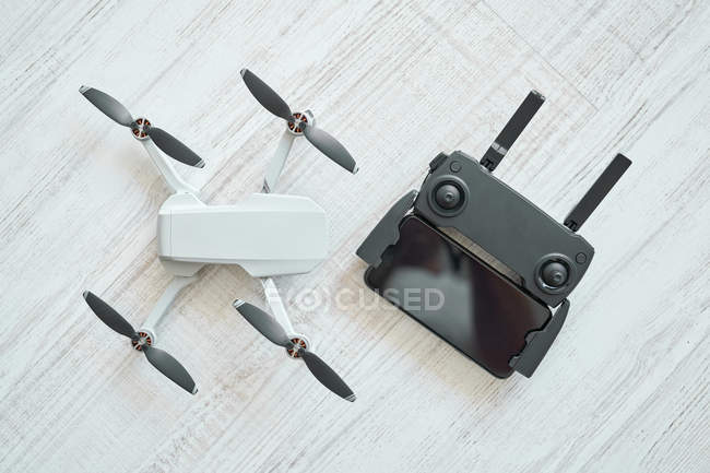 Drone and the remote control on floor — Stock Photo