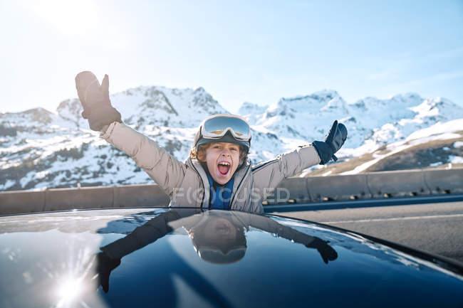 Восхитительный мальчик в шлеме с очками улыбается, глядя в камеру с поднятием рук из окна автомобиля в солнечный день на горнолыжном курорте — стоковое фото
