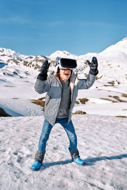 Full body of happy funny boy in outwear standing on snow and exploring virtual reality on sunny winter day in mountains — Stock Photo
